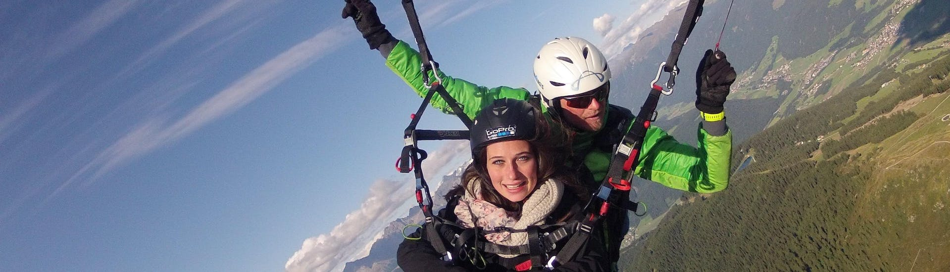 During the Tandem Paragliding over Campo Tures from Acereto with Tandemflights Kronplatz, a young woman is enjoying the view over the surrounding mountain scenery.