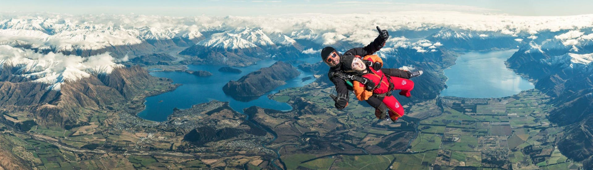 A tandem master from Skydive Wanaka and his passenger are in the middle of their Tandem Skydive in Wanaka - 12,000ft with Queenstown Transfer, above the spectacular mountainscape around Lake Wanaka.
