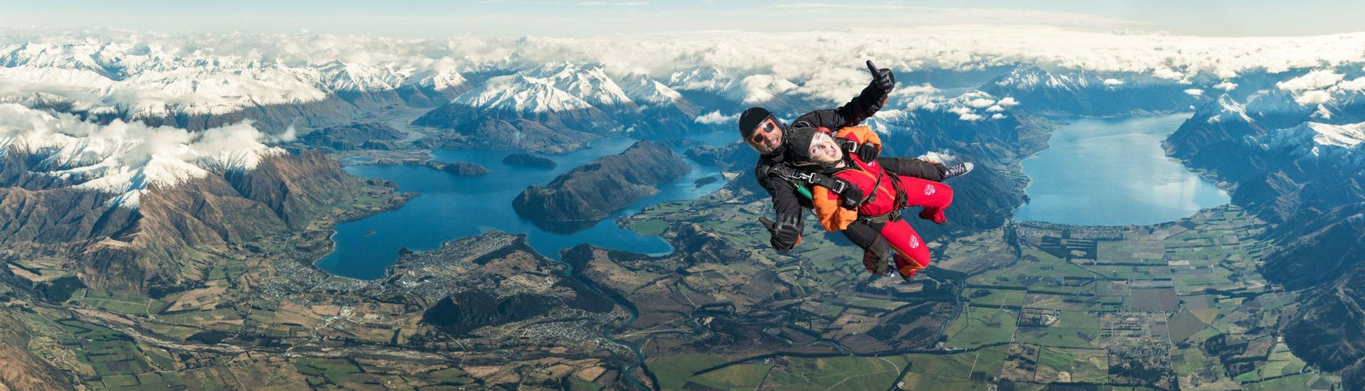 A tandem master from Skydive Wanaka and his passenger are in the middle of their Tandem Skydive in Wanaka - 9,000ft with Queenstown Transfer, above the spectacular mountainscape around Lake Wanaka.