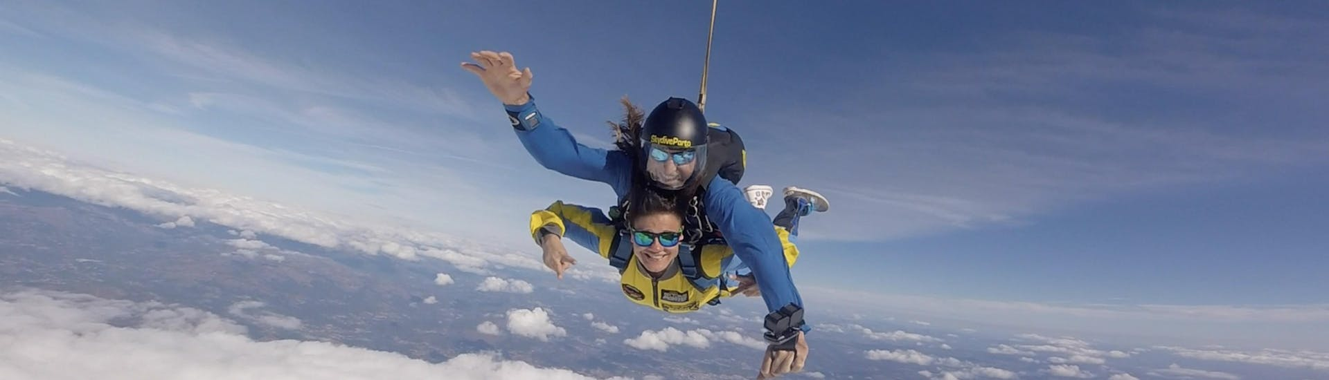 A tandem master from Skydive Porto and his Student are smiling at the camera as the fall freely through the skies while skydiving in Porto.