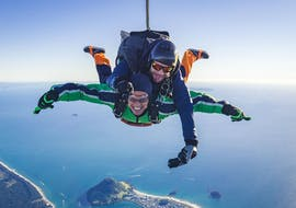 A tandem student is visibly enjoying himself while Tandem Skydiving in Tauranga with his tandem master from Skydive Tauranga.