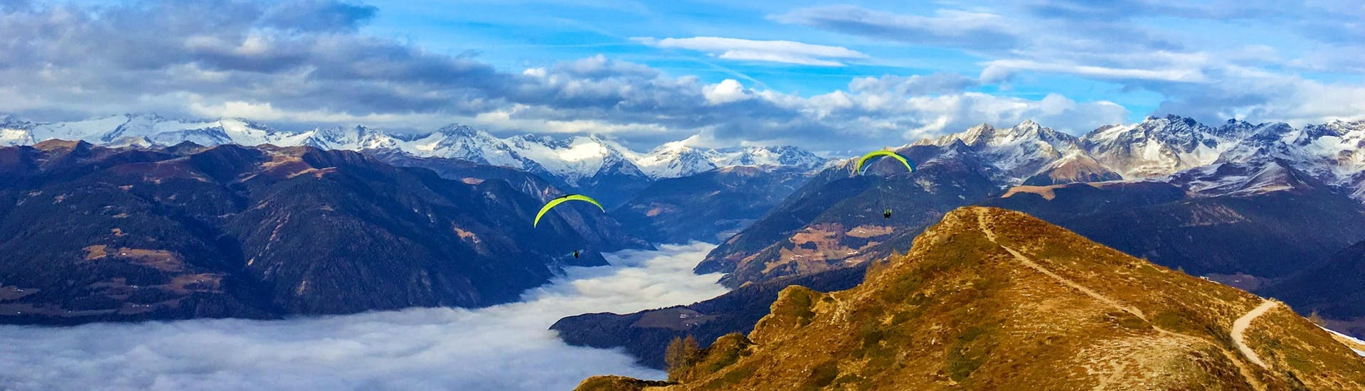 Two paragliders from Tandemflights Kronplatz are gliding over the beautiful mountain scenery around Plan de Corones and the Puster Valley.
