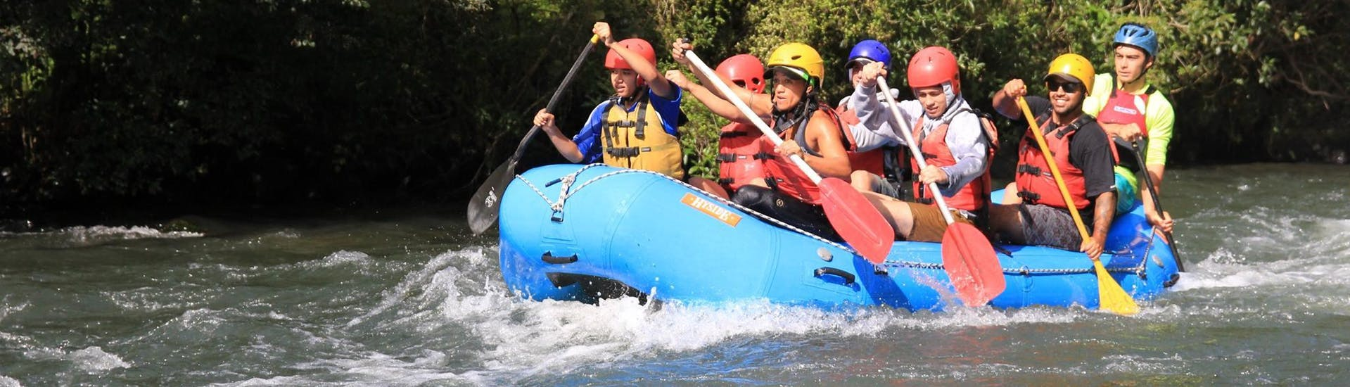 A group of friends is paddling during a calmer passage of Tarawera River Rafting in Kawerau with Rafting Adventure Rotorua.