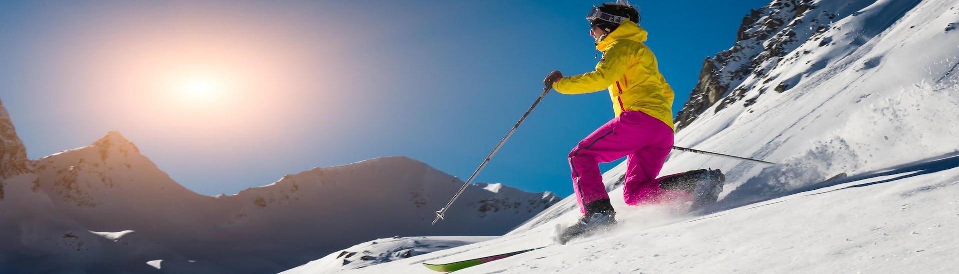 Sous un grand soleil, une skieuse glisse sur une piste de ski lors d'un Télémark Privé - Tous Niveaux & Âges organisé par ESI First Tracks Courchevel.