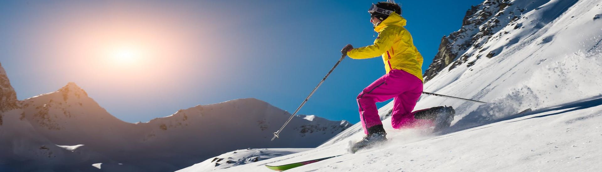 A skier is gliding down a ski slope in telemark position during one of the Telemark from beginners to pros with Konrad Herbert - Skischule Kitzbüheler Horn.