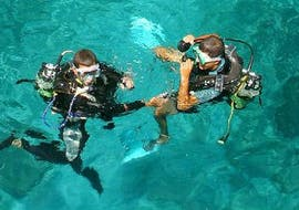 Two persons are preparing for the Trial Scuba Diving in Réserve Cousteau for Beginners with Les Heures Saines Guadeloupe.