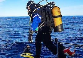 Un débutant bien équipé saute du bateau dans l'eau pendant son Baptême de plongée à pour Débutants à Cerbère-Banyuls avec Plongée Cap Cerbère.