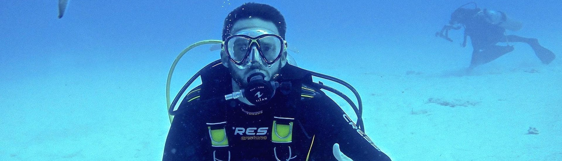 Boy diving with a fish during his Trial Scuba Diving in Nice (20min) with the provider Chango Diving in Nice.