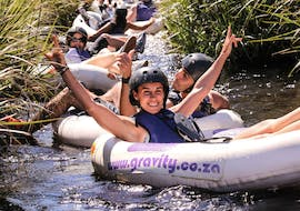 A young woman is smiling at the camera whilst Tubing on Palmiet River in Kogelberg Nature Reserve with Gravity Adventures.