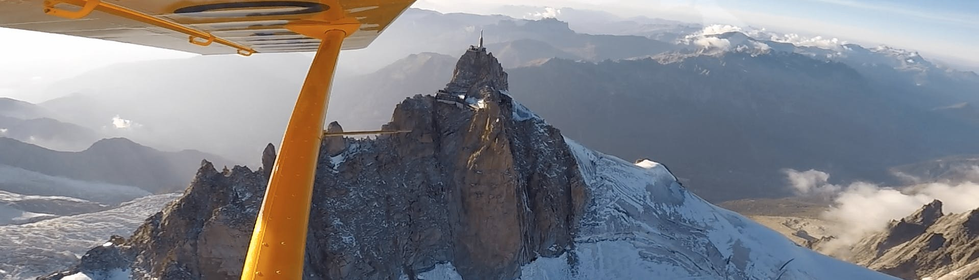 The tourist and his pilot are contemplating the Aiguille du midi during an Ultralight Aircraft flight above the Mont Blanc Massif.