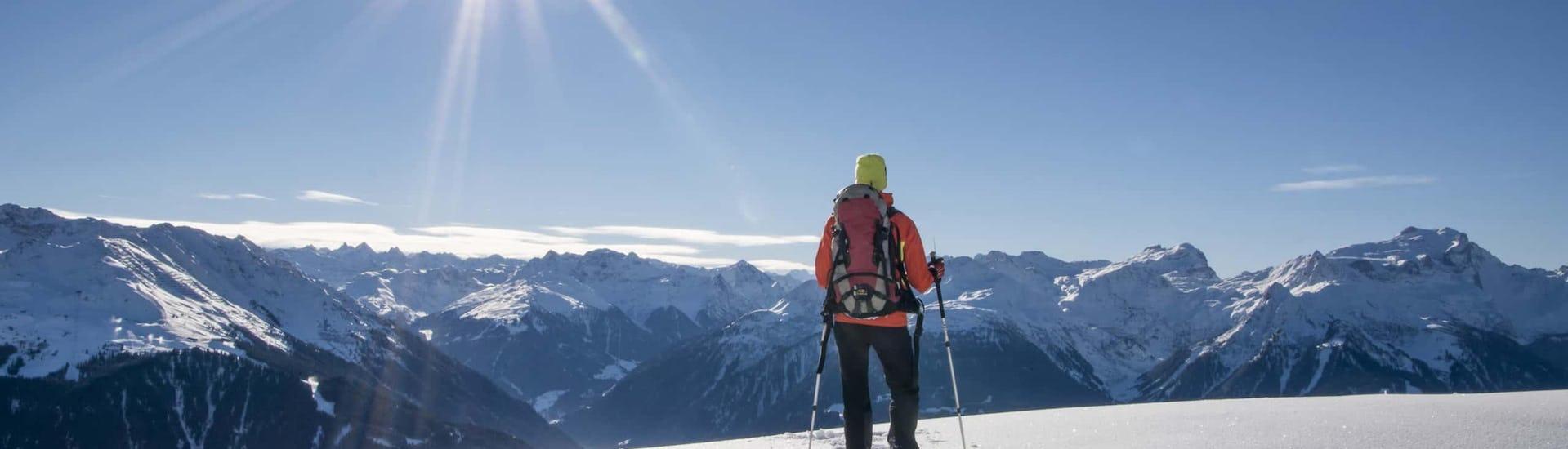 """Eine Person blickt bei der Aktivität """"½-tages Schneeschuhtour zum Kennenlernen"""" mit dem Anbieter Mountain Sports Mayrhofen auf das umliegende Bergpanorama."""