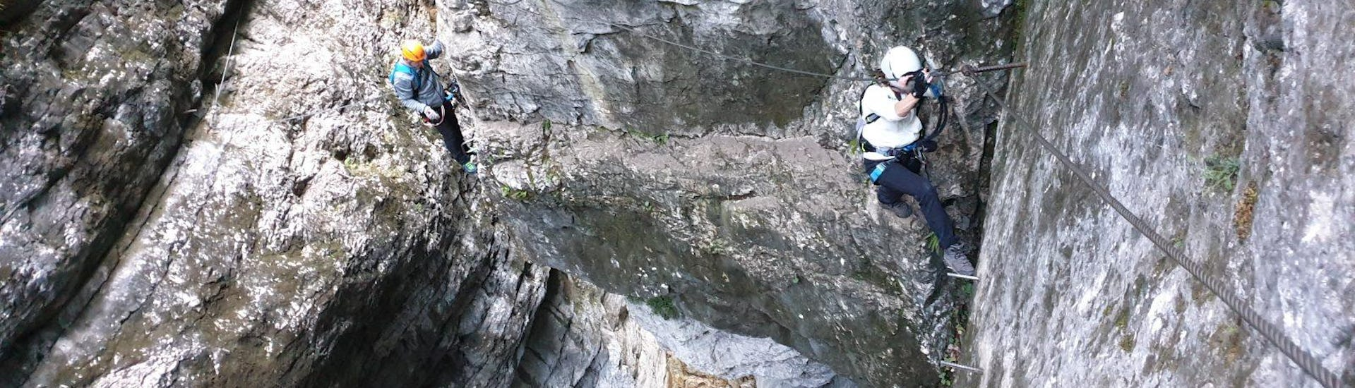 "Two people climbing up the steep cliffs of ""Gamsleckenwand"" on their Via Ferrata Tour for Adventurers with the experienced instructor from Bergführer Salzburg."