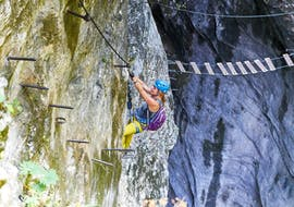 """A woman climbing up the steep """"Gamsleckenwand"""" on her Via Ferrata Tour for Adventurers at Postalm with the experienced guides from Bergführer Salzburg."""