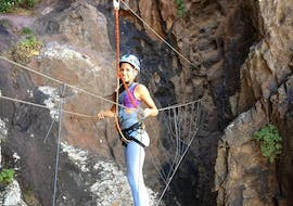 A woman skillfully overcomes the obstacle during the Vía Ferrata at Barranco de Berriel in Gran Canaria organised by Mojo Picón Aventura.