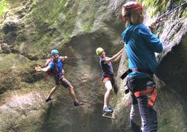 Three participants of the Via Ferrata along Rio Sallagoni are smiling at the camera during the activity organized by LOLgarda.