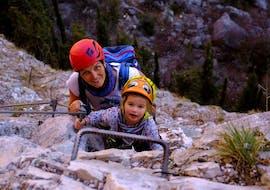 Ein kleines Mädchen steht mit dem Guide von Skyclimber während dem Klettersteig für Klein und Groß - Colodri vor seinem ersten Klettersteig.