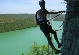 """A man is enjoying Via Ferrata """"Lac de Vouglans"""" - Moirans activity with La Boîte à montagne."""