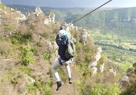 "A man is doing zip line during his activity Via Ferrata ""Nature"" in the Gorges du Tarn  with B&ABA Sport Nature."