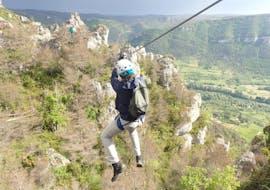 """Un homme fait de la tyrolienne pendant son activité Via Ferrata """"Nature"""" dans les Gorges du Tarn avec B&ABA Sport Nature."""