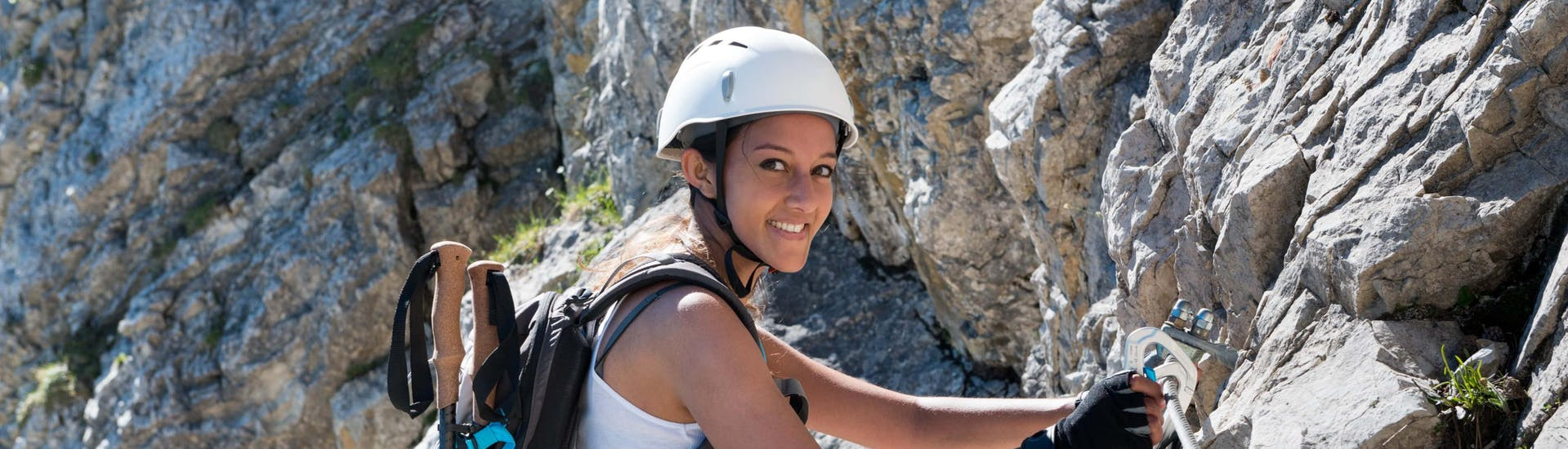 A young woman traversing along a via ferrata in the via ferrata hotspot of South Africa.
