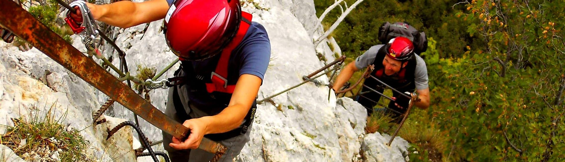 Two participants in the Via Ferrata Via dell'Amicizia organized by Skyclimber proceed in the direction of the photographer.