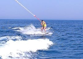 A guy tries to keep his balance on the wakeboard towed by the boat, during Wake Boarding in Ramla Bay with Vitamin Sea.