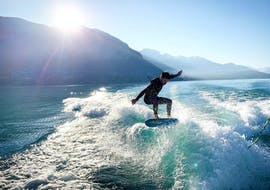 A man is skillfully surfing a wave during his Wakeboard & Wakesurf Lessons on Lake Annecy with Le Spot.