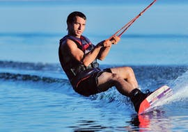 Un homme se concentre sur le wakeboard à Santorin tout en étant remorqué par un bateau à moteur de Crazy Sports.
