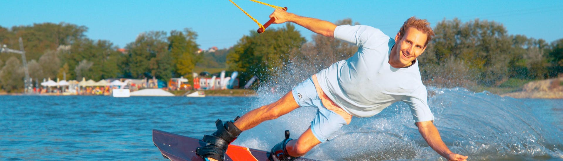 Happy guy is wakeboarding on a beautiful day