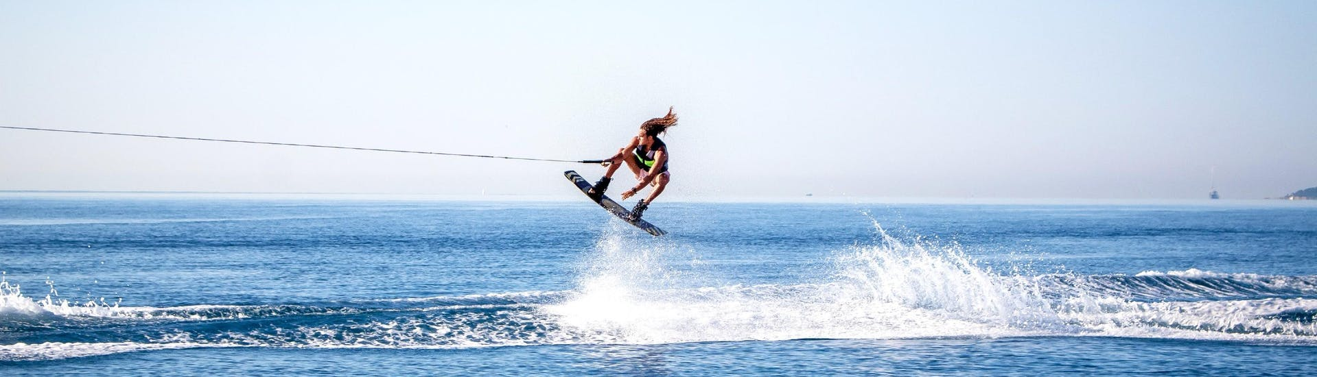 A man is doing a jump during his Wakeboarding & Wakesurfing tour in Villeneuve-Loubet with Plage des Marines.