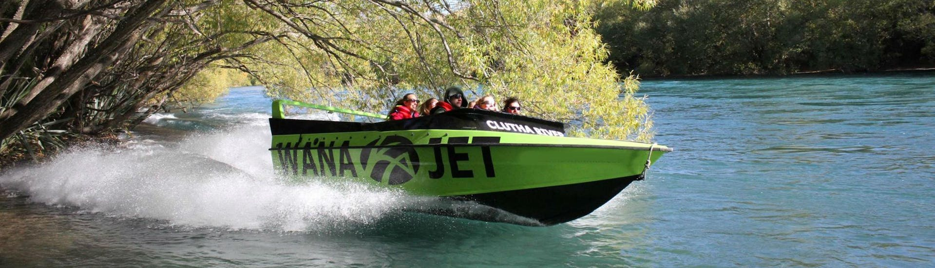 A jet boat operated by Lakeland Wanaka is speeding along Clutha River during the Wanaka Jet Boat Tour.