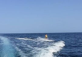 A guy skiing on the sea waves carried by the boat, during Water Skiing at Ramla Bay with Vitamin Sea.