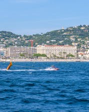 A speedboat is whizzing across the clear blue waters of the French Riviere while pulling a crazy sofa, one of the many different types of water sports in Cannes.