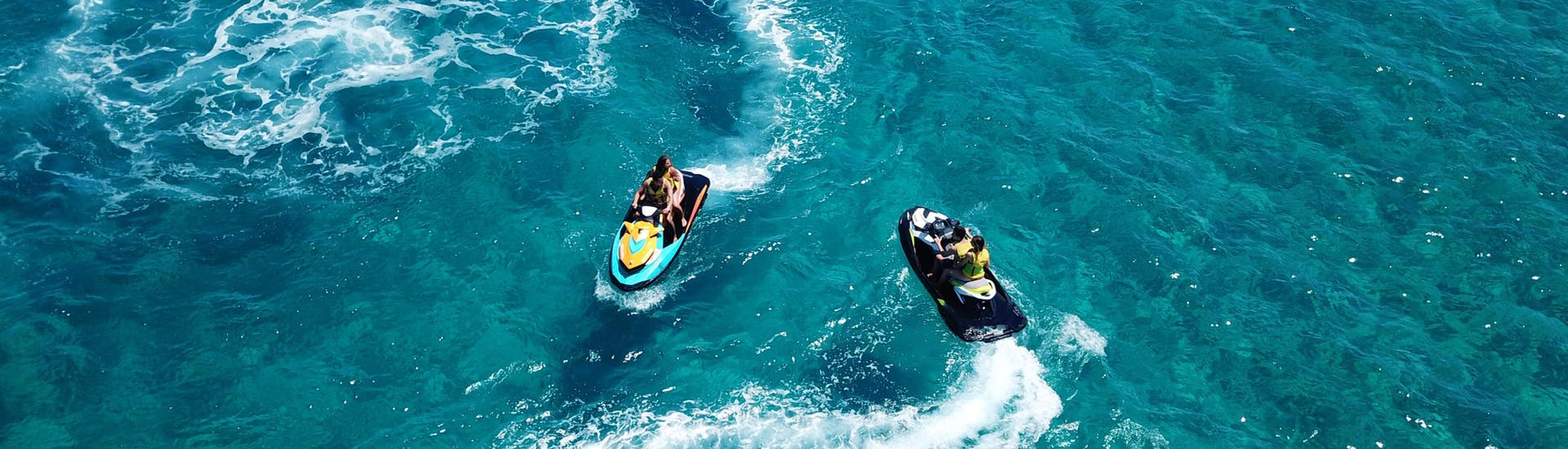 A group of friends riding a banana boat in the holiday destination of Santorini.