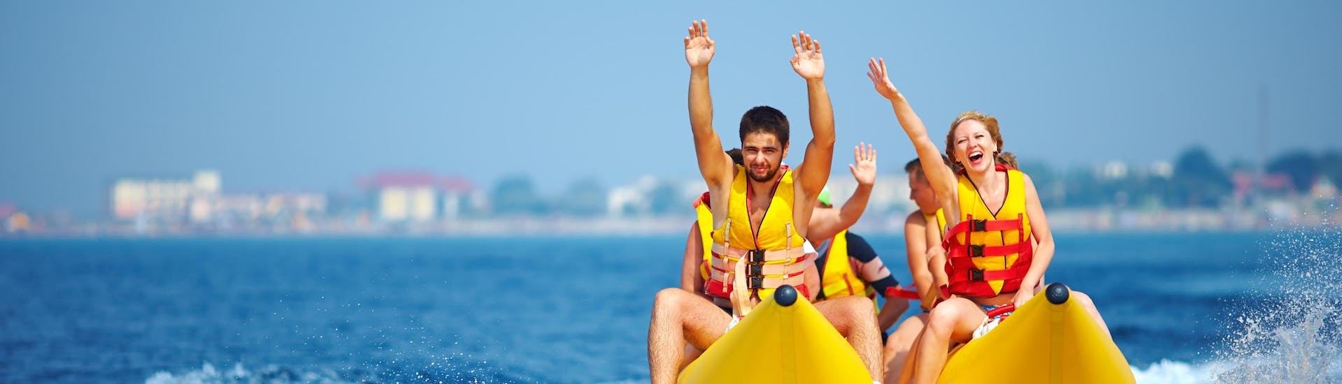 A group of friends riding a banana boat in the holiday destination of Puerto Colón.