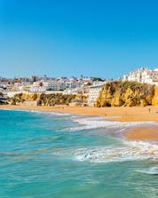 A view from the beach with the city in the background and the ocean where you can do water sports activities in Albufeira.