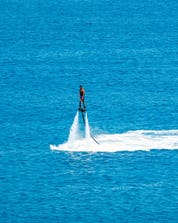 A photo of a brave young man mid-air above the ocean in Greece where you can do different water sports activities.
