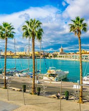 A view of the port with the city and the ocean where you can do water sports activities in Málaga.