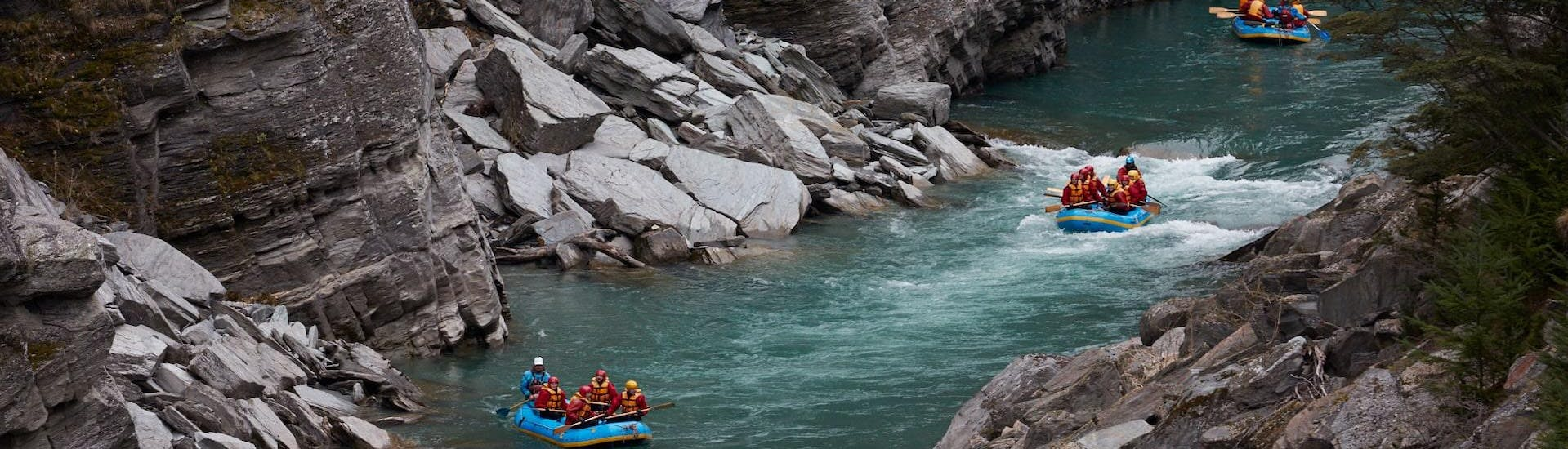 Participants of the White Water Rafting from Queenstown on Shotover River are observing rafts passing by with the local guides from Go Orange
