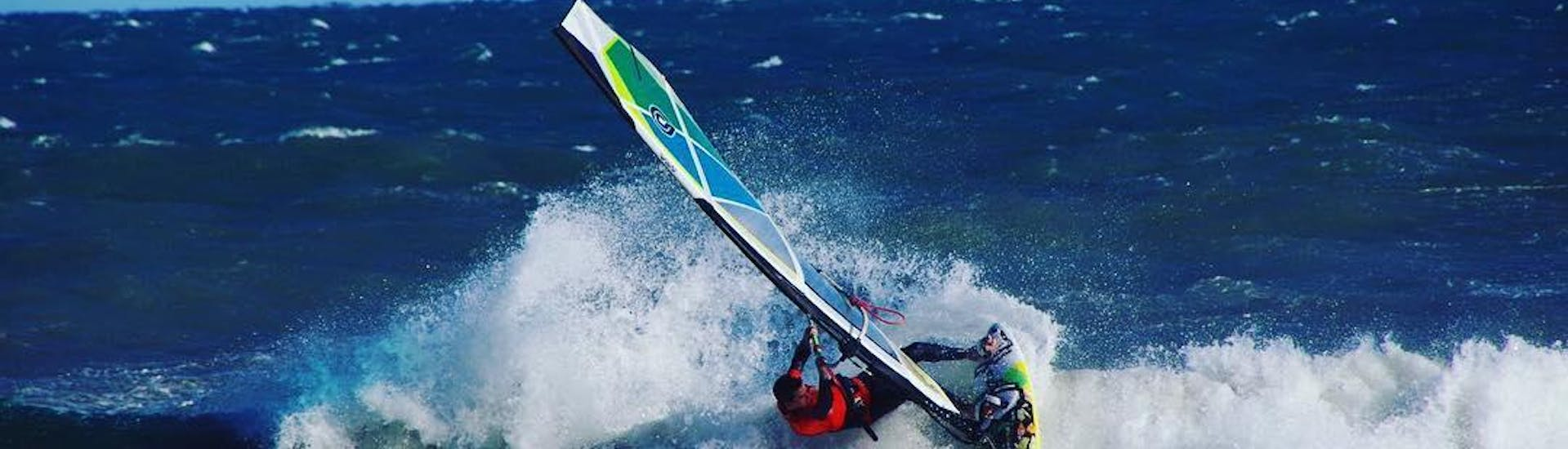 A man is practicing his first turns in the water during the windsurfing lessons in Cullera for beginners with Anywhere Watersports.
