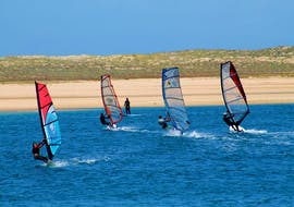 Four windsurfers are practicing their technique during the Windsurfing Lessons at Lagoa de Albufeira in Sesimbra under the guidance of an experienced intructor from Meira Pro Center.
