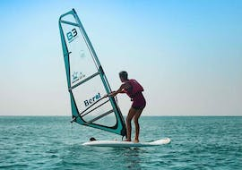 A man is standing up for the first time in the water with his windsurfing lessons in Cullera for beginners from Anywhere Watersports.