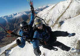 A tandem master from Skytrek Queenstown and his passenger are flying over the snow-capped peaks of Otago while Paragliding in Queenstown - Winter.