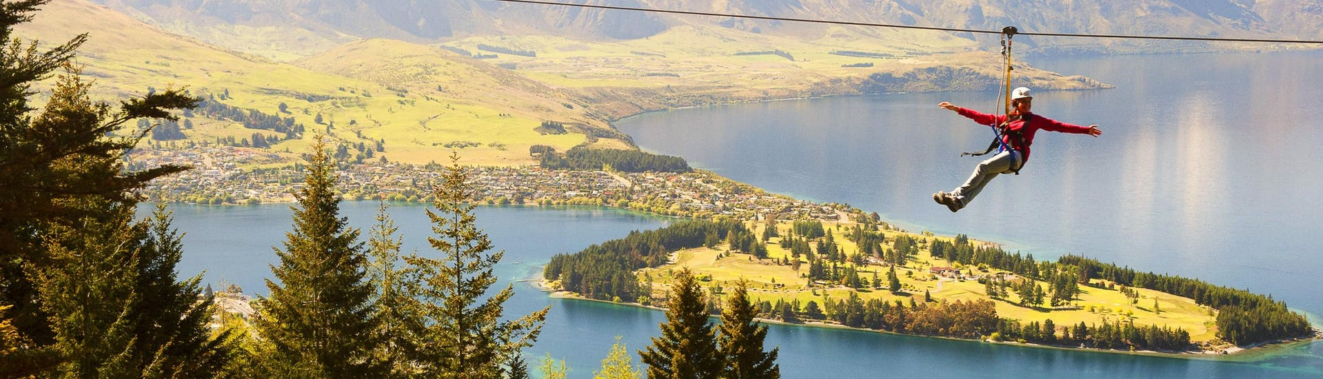 A girl looks at the panorama from the zipline during Zipline in Queenstown - Moa: 4 Lines of the Ziptrek Ecotours Queenstown, behind her a lush landscape and the wonderful Lake Wakatipu.