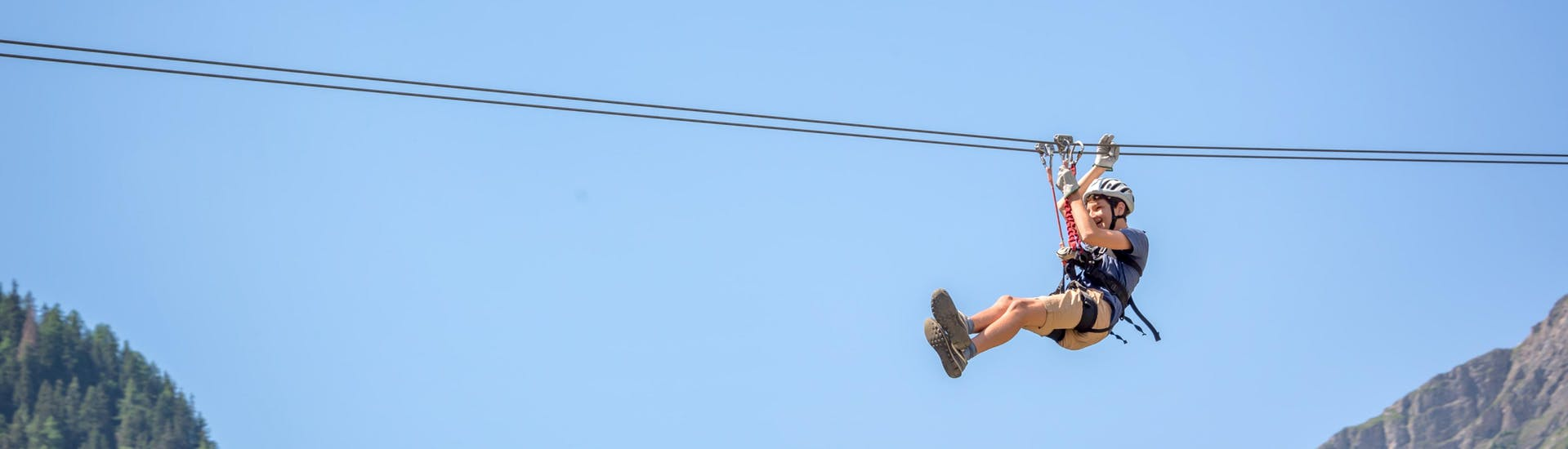 Un giovane uomo in volo sospeso da una zipline nell'hotspot di zipline presso Ardèche.