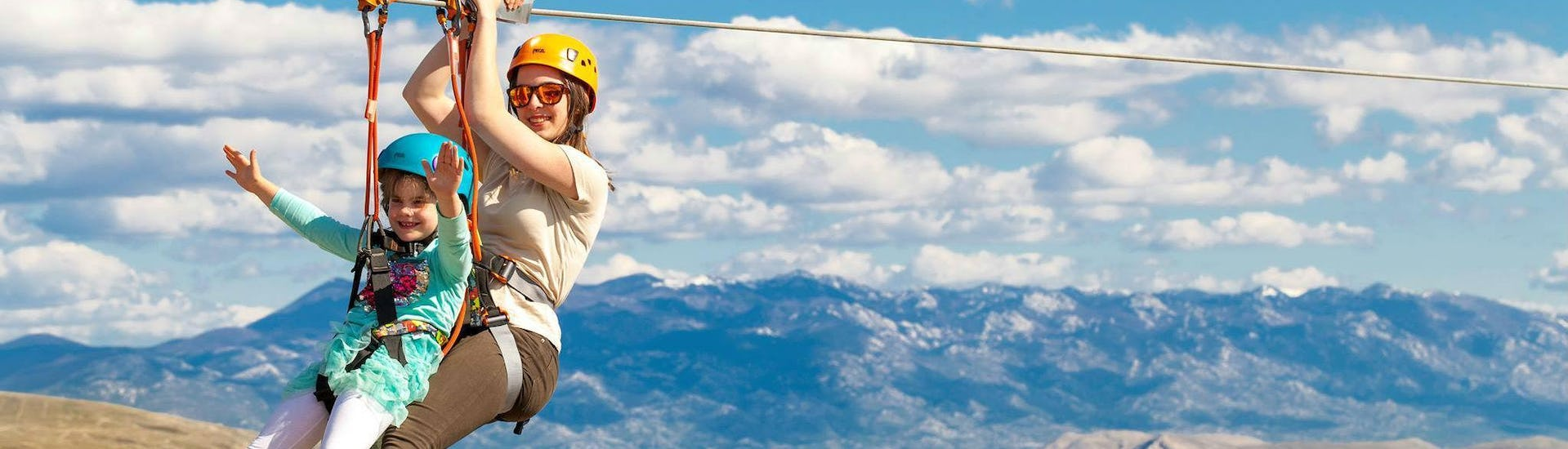 """A small happy girl is gliding on a zipline with a qualified guide from Edison Zipline Krk during the zipline tour """"Explore Krk"""" on the Island of Krk."""