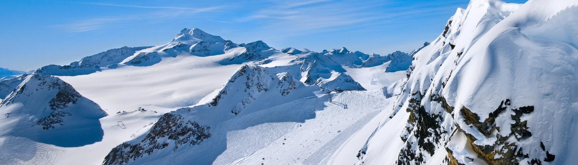 View of a snowy mountain top in a ski resort, in which ESKIMOS Ski & Snowboard School  Saas-Fee carries out ski lessons.