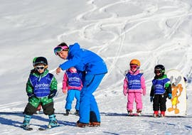 """A group of children is doing an exercise during the Kids Ski Lessons """"Polar Bears"""" (3-5 y.) with Altitude Ski School Verbier & Gstaad."""