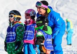 Trois enfants admirent un skieur pendant les cours de ski pour enfants (6-15 ans) d'Altitude Ski School Verbier & Gstaad.