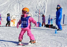 A child is skiing for the first time during the Private Ski Lessons for Kids of All Ages in Verbier with Altitude Ski School Verbier & Gstaad.